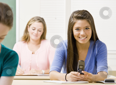 Student text messaging on cell phone in classroom stock photo, Student text messaging on cell phone in classroom by Jonathan Ross