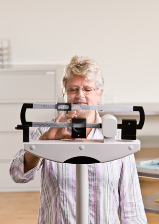 Senior woman weighing herself in doctor?s office stock photo, Senior woman weighing herself in doctor?s office by Jonathan Ross