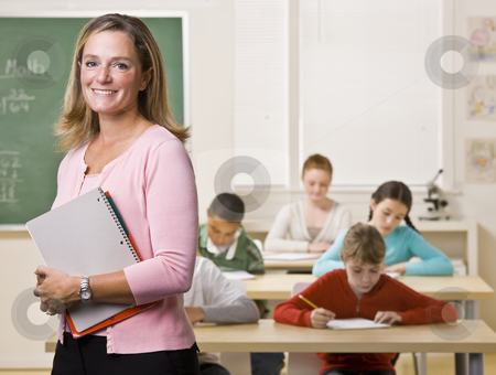 Teacher standing with notebook in classroom stock photo, Teacher standing with notebook in classroom by Jonathan Ross