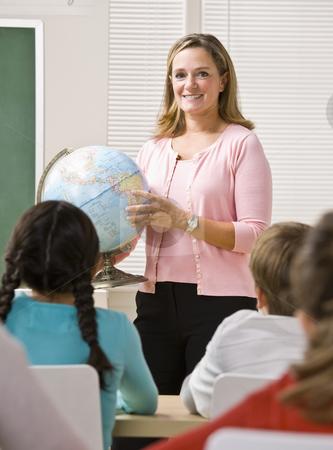 Teacher explaining globe to students stock photo, Teacher explaining globe to students by Jonathan Ross