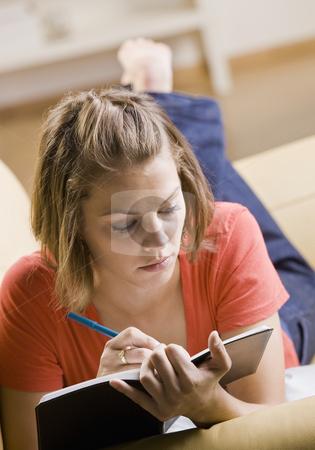 Teenage girl writing in book stock photo, Teenage girl writing in book by Jonathan Ross