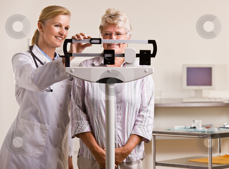 Doctor weighing senior woman in doctor?s office stock photo, Doctor weighing senior woman in doctor?s office by Jonathan Ross