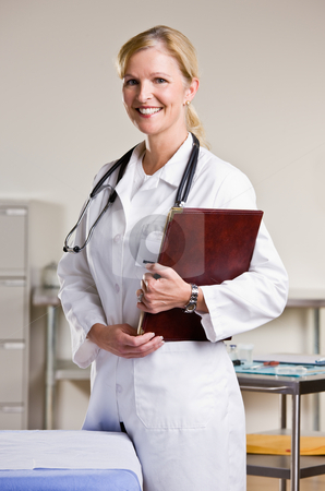 Doctor in doctor?s office holding notebook stock photo, Doctor in doctor?s office holding notebook by Jonathan Ross