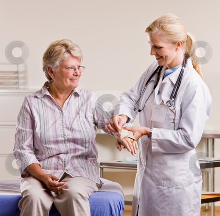 Doctor adjusting senior woman?s wrist splint stock photo, Doctor adjusting senior woman?s wrist splint by Jonathan Ross