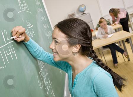 Student writing on blackboard stock photo, Student writing on blackboard by Jonathan Ross
