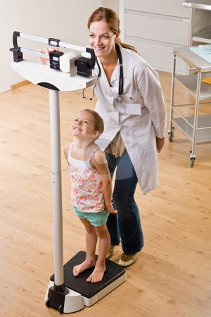 Doctor weighing girl in doctor?s office stock photo, Doctor weighing girl in doctor?s office by Jonathan Ross
