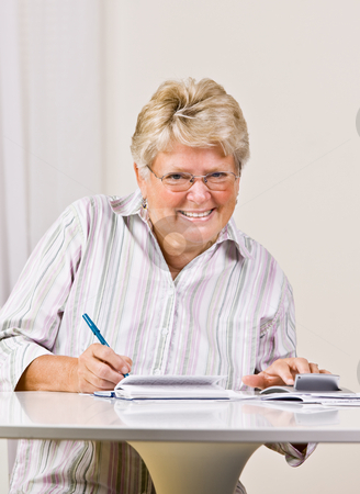 Senior woman writing checks stock photo, Senior woman writing checks by Jonathan Ross