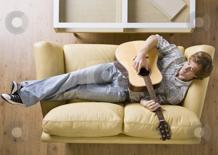 Man laying on sofa playing guitar stock photo, Man laying on sofa playing guitar by Jonathan Ross