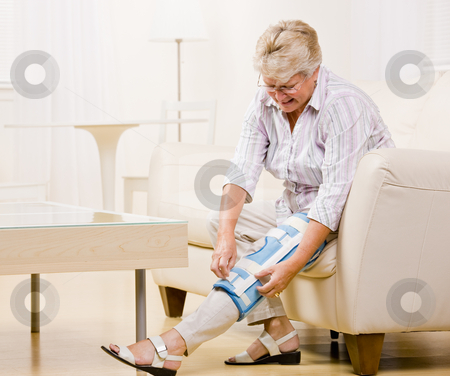 Senior woman adjusting knee brace stock photo, Senior woman adjusting knee brace by Jonathan Ross