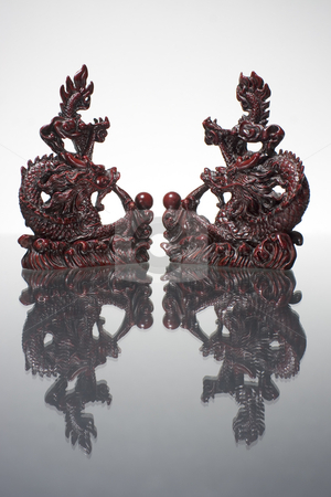 4 way dragon mirror stock photo, Two dragon statue reflecting on a grey surface by Yann Poirier