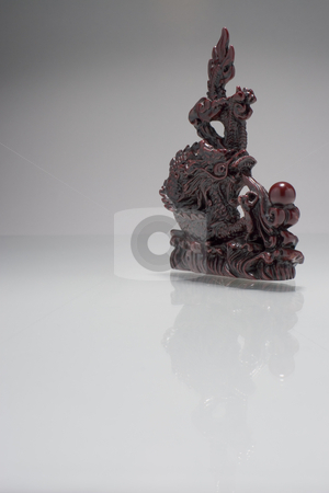 Floating dragon stock photo, Asian dragon statue floating on a white reflective surface by Yann Poirier