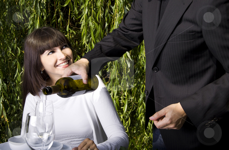 Lunch in the garden stock photo, Waiter filling a glass of white wine for a woman dining in a garden by Daniel Kafer