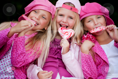 Eating a lollipop stock photo, Happy children having pink clothes and a lollipop by Frenk and Danielle Kaufmann