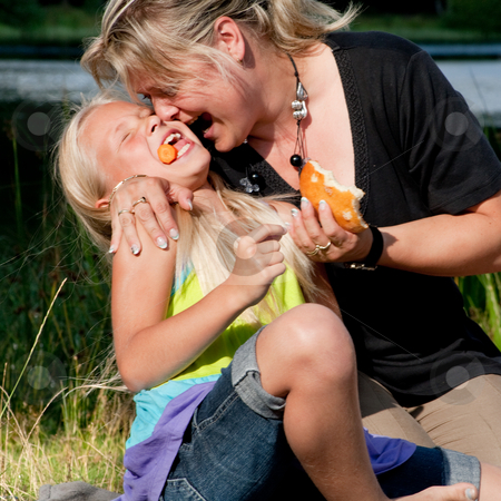 Mother and daughter eating stock photo, Happy children having fun in the park by Frenk and Danielle Kaufmann