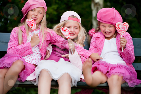 3 playfull sisters stock photo, Happy children having pink clothes and a lollipop by Frenk and Danielle Kaufmann