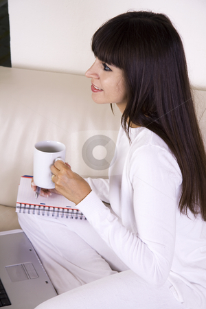 Drinking tea and working stock photo, Beautiful latina woman is sitting on a cream color sofa with her computer and a cup of tea working from home by Daniel Kafer