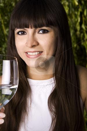 Woman drinking white wine stock photo, Beautiful stylish latina woman is drinking champagne by Daniel Kafer