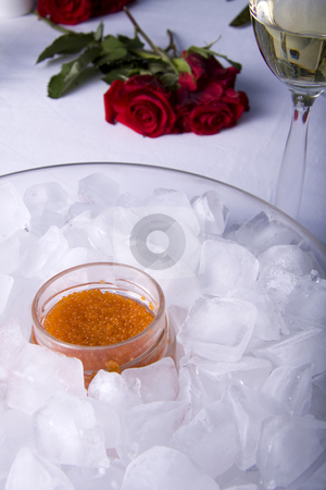 Red caviar on ice stock photo, Red caviar in a glass jar surrounded by ice cubes and a rose by Daniel Kafer