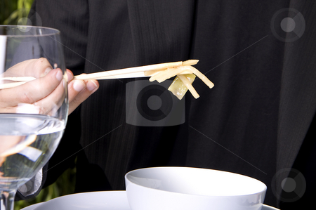 Eating with chop sticks stock photo, Man in a black suit is eating asian food with chop sticks by Daniel Kafer