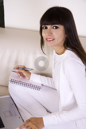 Woman working from home stock photo, Beautiful latina woman is sitting on a cream color sofa with her computer and a cup of coffee working from home by Daniel Kafer