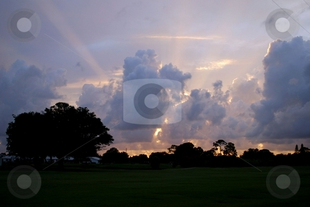 Golf course at sunset stock photo, Sunset rays over a golf course by Charles Bacon jr