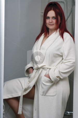 Red hair model in bathrobe stock photo, Red hair woman model in white bathrobe standing in bathroom showing her leg by Yann Poirier