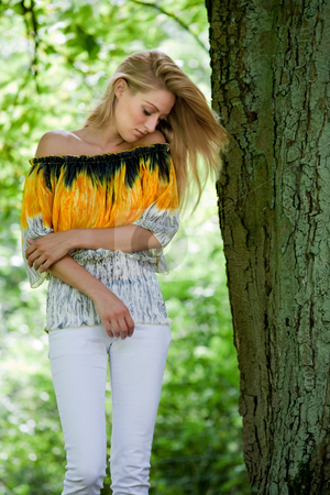 Blond beauty in yellow blouse posing next to a green tree stock photo, Beautifull blond standing next to a tree in thoughts. by Frenk and Danielle Kaufmann