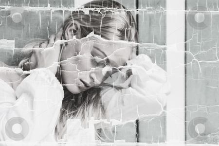 Cracked image of sad blond stock photo, Blond woman looking sad. The design gives a cracked image to support the serenity and sadness. by Frenk and Danielle Kaufmann