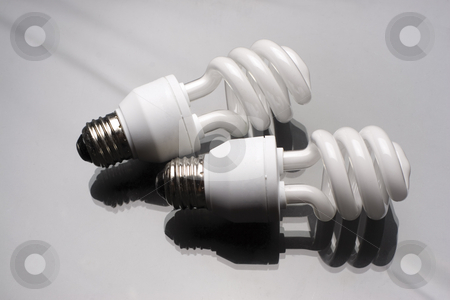 Two spiral bulbs stock photo, Two compact fluorescent light bulb on reflective surface by Yann Poirier