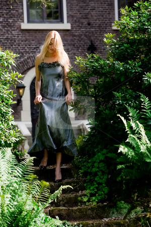 Blond beauty in a castle garden dressed for gala stock photo, Beautifull blond in gala dress walking walking down some stairs in a castle garden by Frenk and Danielle Kaufmann