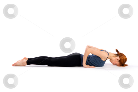 Fit Woman Practising Yoga stock photo, Young slim woman doing yoga exercise called Bhujangasana, isolated on white background. by Rognar