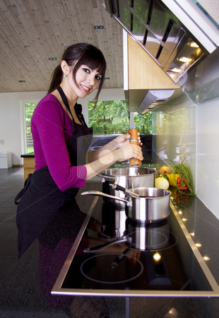 Woman cooking stock photo, House wife adding spices to the sauce by Daniel Kafer