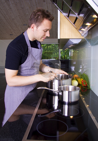 Man cooking stock photo, Man cooking and stirring in the casserole by Daniel Kafer