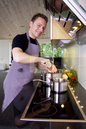 Chef cooking stock photo, Chef adding pepper to the saucepan using a grinder by Daniel Kafer