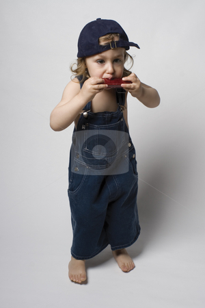 Kid playing harmonica stock photo, Two year old boy playing harmonica on white background by Yann Poirier