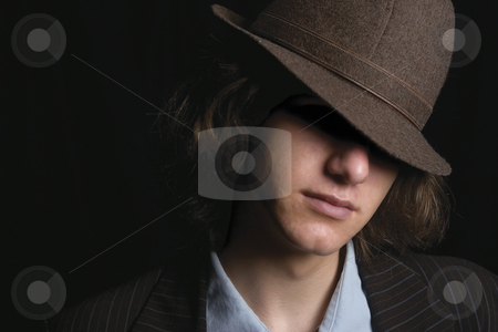 Young man with hat stock photo, Young man faces partly hidden by hat by Yann Poirier