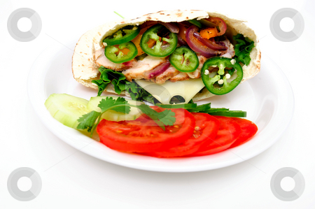 Pita Bread Sandwich stock photo, Grilled chicken flatbread sandwich with lettuce, swiss cheese, grilled onions and bell pepper with sliced jalapeno chili. Sliced tomatoes, cucumber and a sprig o cilantro on a white plate by Lynn Bendickson