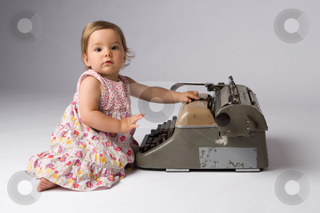 Baby Girl with an Antique Toy stock photo, Cute baby girl posing with an antique typewriter. by Rognar