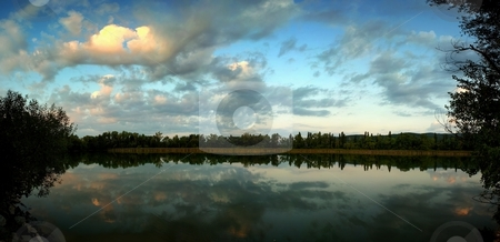 Panorama of a lake in sunrise with one illuninated cloud stock photo, Panorama of a lake in sunrise, smooth surface with reflection of clouds. One cloud illuminated by rising sun by Juraj Kovacik