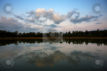 Sunrise over lake stock photo, Lake in early morning with sky reflection on smooth water surface by Juraj Kovacik