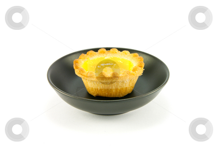 Lemon Jam Tart stock photo, Single small yellow lemon jam tart in a small black dish with a white background by Keith Wilson
