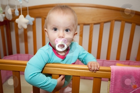 In my crib stock photo, Cute Caucasian baby girl playing in her crib during a day. by Mariusz Jurgielewicz