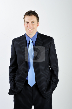 Man Wearing Suit stock photo, A young man is wearing a suit and a blue tie.  He is smiling at the camera.  Vertically framed shot. by Zee Images