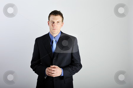 Man Wearing Suit stock photo, A young man is wearing a business suit with a blue tie, and is looking at the camera.  Horizontally framed shot. by Zee Images