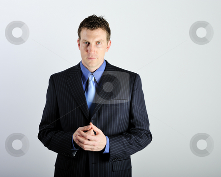 Man Wearing Business Suit stock photo, A young man is wearing a suit and a blue tie.  He is looking at the camera.  Square framed shot. by Zee Images
