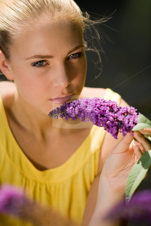 See me smelling my alternative medicine stock photo, Portrait of a blond woman smelling a purple flower.
