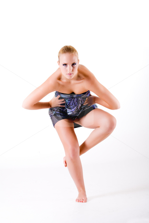 Balancing high fashion style while looking at you stock photo, Blond model in blue dress balancing on one leg.
