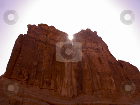 Suncrest stock photo, The sun rising over a red sandstone cliff in Arches National Park, Utah. by Jeremy Tritchler