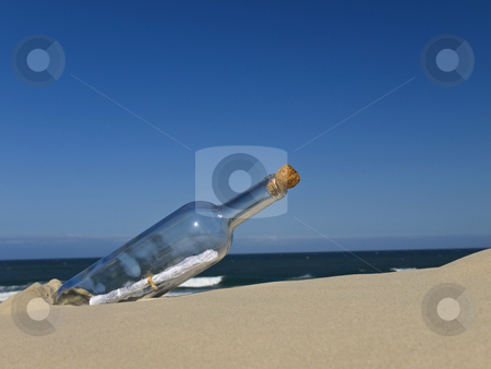 Castaway stock photo, A bottle with a message inside is buried on the beach. by Ignacio Gonzalez Prado