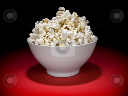 Popcorn bowl stock photo, A bowl full of popcorn under the spotlight. by Ignacio Gonzalez Prado